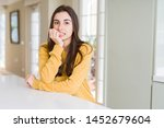 Stock photo beautiful young woman wearing yellow sweater looking stressed and nervous with hands on mouth 1452679604