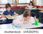 little schoolgirl drawing while ... | Shutterstock . vector #145282951