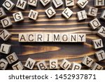 Small photo of acrimony wooden cubes with letters, bitter full of anger concept, around the cubes random letters, top view on wooden background