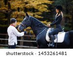 girl riding a horse in park in Autumn near lake in the mountains. horseman and horsewoman on horse galloping. jockey teach woman to ride. equestrian sport concept. training to ride on horse. vacation