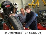 Small photo of Teacher with students in mechanics working on bike