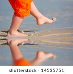 Young Child Kicking Sand By...