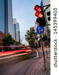 city street in the evening in the city of Frankfurt, Germany, with light trails of driving cars - stock photo