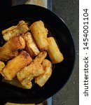 Small photo of Singkong goreng is Indonesian traditional food, usually eaten in the morning or evening when the weather is rather cold, made from cassava fried with salt and garlic spices that have been mixed