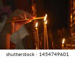 A Woman Hand Lit A Candle In...