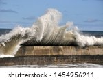 Waves crashing over sea wall at Seahouses in a rough sea