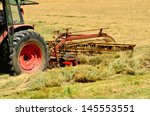 Small photo of Agriculture tractor pulling a rotary bar tine rake through a field of cut grass hay to windrow for the baler for winter livestock feed