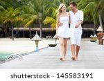 Couple Walking On Wooden Jetty