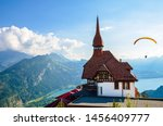 Stunning view of the top of Harder Kulm in Interlaken, Switzerland photographed in summer with paragliders flying around. Hilly Alpine landscape and Lake Thun in background. Paragliding, sunset - stock photo