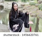 Beautiful Asian woman in black and white Chinese costume clothes hanfu sitting on rock in middle of stream looking with lotus lantern in hand, traditional ancient Chinese beauty, time travel fiction.