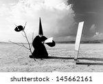 Strange figure in black cloak with the splinter of mirror in desert. Artwork - stock photo