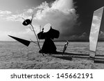 Strange figure in black cloak with the mirror face in desert. Artwork - stock photo