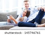 couple on sofa with digital... | Shutterstock . vector #145746761
