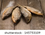 Four Dry Fish On Wooden Table