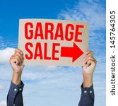 Small photo of Two hands holding brown cardboard with garage sale on blue sky background