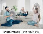 Small photo of Photo of foster family four members spend leisure time rejoicing pillows fight giggle sit couch living room