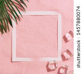 Small photo of Summer day scene with ice cubes and tropical palm leaf on pink sand pastel color background. Minimal sunlight tropical flat lay arrangement.