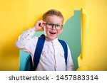 Small photo of Child boy with book and bag breaking through yellow paper wall. Happy smiling kid go back to school, kindergarten. Success, motivation, winner, genius concept. Little kid dreaming to be superhero