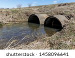 Storm water runoff flowing from drainage ditch into concrete culverts under a road