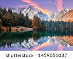 Impressive Autumn landscape during sunset.  The Fusine Lake in front of the Mongart under sunlight. Amazing sunny day on the mountain lake. concept of an ideal resting place. Creative image. - stock photo