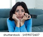 Small photo of Young upset woman on sofa using control remote zapping bored of bad TV shows and programing . Looking disinterested, aloof and sleepless. People, too much bad television and Sedentary lifestyle.