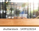 Small photo of Wood table in blurry background of modern restaurant room or coffee shop with empty copy space on the table for product display mockup. Interior restaurant counter design concept.
