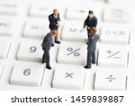 Small photo of Business mans standing on calculator. Interest rate financial and mortgage rates. Compound interest rate calculation. Risk management financial and managing investment percentage interest rates.