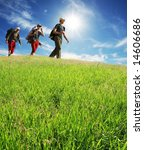 Hikers on green meadow - stock photo