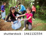 Small photo of Group of active people picking up litter in nature, a plogging concept.