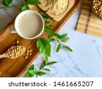"""Small photo of Top view of soymilk cups,soybean seeds on wooden spoon and soy milk powder in a wooden plate background white marble table, is a healthy drink for women because of the """"isoflavones"""" substance"""