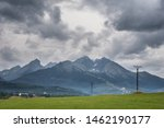 Green meadow with electric poles and the Tatra mountains with dramatic dark storm clouds in the background, Slovakia, Tatranska Lomnica.  - stock photo