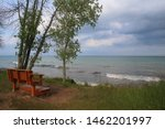 Beautiful summer landscape in a state park. Lake Michigan scenic view with wooden bench on the beach at the Harrington Beach State Park, Wisconsin, USA. Wisconsin nature background.