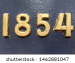 The year 1854 from a cast-iron inscription produced that year. Painted in gold on a black background