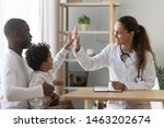 Small photo of Happy mixed race african cute little child boy give high five to female doctor pediatrician welcome small kid patient and his dad at medical check up appointment, children medical health care concept