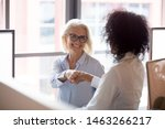 Small photo of Smiling middle-aged female employee shake hand greeting get acquainted with colleague at workplace, positive businesswoman handshake introduce to woman coworker in office. Cooperation concept