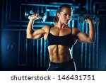 Woman bodybuilder with dumbbells on wall background. - stock photo