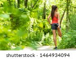 Small photo of Fit stretch woman stretching quad leg muscle standing getting ready to run jogging outside in summer nature forest park green trees background. Fitness runner athlete running girl.