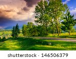 road in the mountains among the trees near the clearing. red and purple clouds in the evening - stock photo