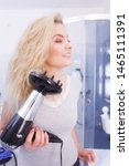 Small photo of Haircare. Beauty long haired blonde woman drying hair in bathroom. Smiling girl blowing wind on wet head using hairdryer, doing curls with diffuser nozzle.