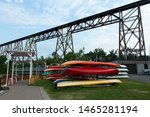 Pile of colourful kayaks in the Cap-Rouge waterfront area nautical park installations with a 1908 railway trestle bridge in the background, Quebec City, Quebec, Canada