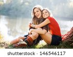 Two Young Women Sitting On...