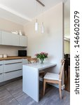 Bright space - a white modern kitchen with dining space - stock photo