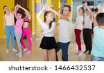 Small photo of Group of tweens practicing vigorous jive movements in dance class with female coach