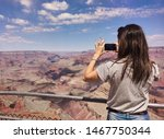 Girl taking a picture with her mobile in the Grand Canyon of the Colorado.