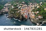 Aerial view of Riomaggiore Bay. Colorful italian houses on rocky coast. Boats floating in the sea. Cinque Terre, Italy.