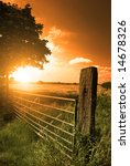 A Farm Fence Leading Into A...