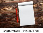 Notepad with red pencil on a...
