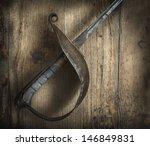 Old fencing sword on wooden background - stock photo