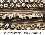 Small photo of interjection - word from wooden blocks with letters, *** concept, random letters around, top view on wooden background