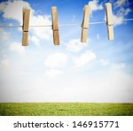 Stock photo clothespin on a laundry line outside with bright blue sky with green landscape 146915771